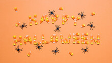 Overhead View Of Candy Corns Arranged As Happy Halloween Text Amidst Artificial Spiders Over Orange Background