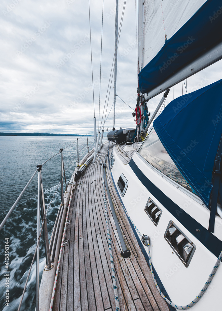 Fototapeta Sloop rigged modern yacht with wooden teak deck sailing near the rocky shore of Jura island on a cloudy day, close-up. Inner Hebrides, Scotland, UK. Sport, recreation, cruise, travel destinations - obraz na płótnie