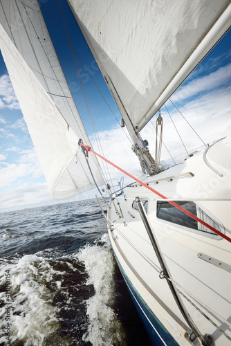 Fototapety, obrazy: White sloop rigged yacht sailing in an open sea on a clear day. A view from the deck to the bow. Cumulus clouds. Transportation, travel, cruise, sport, recreation, leisure activity, racing, regatta