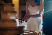 Midsection Of Bride Cutting Wedding Cake While Standing By Bridegroom In Hotel