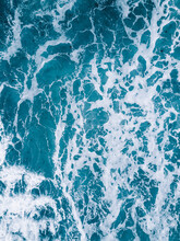 Vertical Shot Of Ocean Waters With Waves Making White Foam