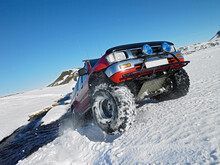Red SUV Crossing River In The Winter On The Icelandic Highlands