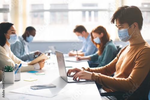 Tela International people wearing medical masks using laptop