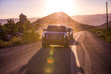 Two Luxury Car Driving On Desert Road In Front Of Sunset In The Desert