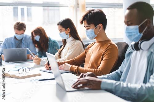 Canvas Print International people wearing medical face masks using laptop