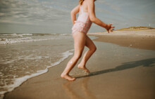 Cropped, In Motion Body Of Young Girl Running On Beach