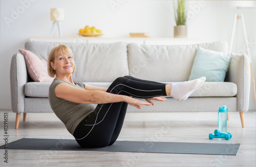 Happy senior woman doing abs exercises on yoga mat at home. Stay fit and healthy during covid quarantine