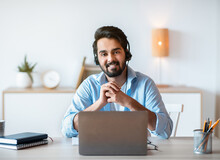 Remote Job. Smiling Arab Man Hotline Manager In Headset Posing At Workplace