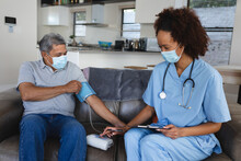 Senior Mixed Race Man With Female Doctor Home Visiting Wearing Face Masks Taking Blood Pressure