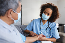 Senior Mixed Race Man With Female Doctor Home Visiting Wearing Face Masks Taking Pulse