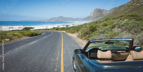 Empty blue car standing by the mountain road near the coast