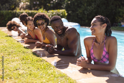 Diverse group of friends smiling and leaning on the poolside