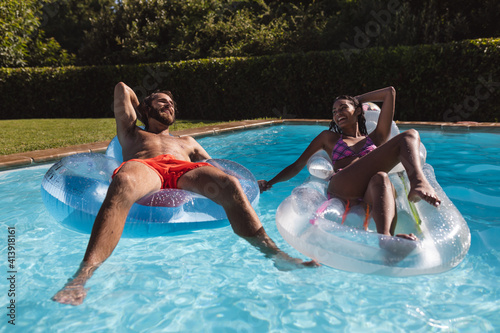 Two diverse male and female friends having fun playing on inflatables in swimming pool
