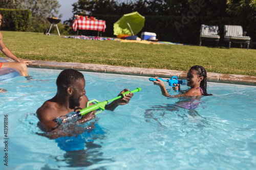Two diverse male and female friends having fun playing with water guns in swimming pool