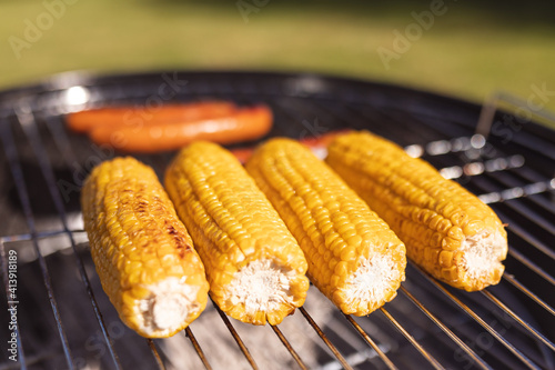 Close up of fresh grilled corns and tasty sausages on barbecue