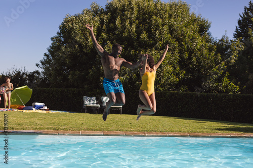 Two diverse male and female friends having fun and jumping into swimming pool