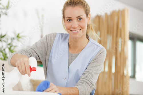 Foto beautiful young housekeeper cleaning and washing kitchen