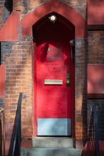 Red Metal Door With Brick Walls Stoop