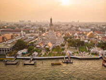 Aerial View Of Wat Arun Pagoda Along The Chao Phraya River At Sunset With Urban Residential District In Background, Khet Phra Nakhon District, Bangkok, Thailand.