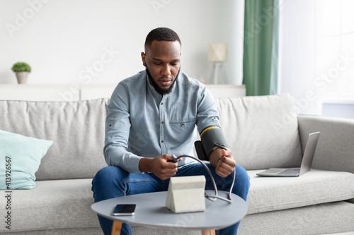 Fototapeta African Man Measuring Arterial Blood Pressure Sitting At Home obraz