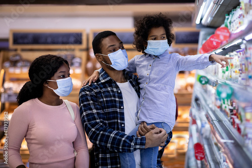 Fototapeta Millennial black family wearing protective masks while shopping for milk products at dairy section of modern supermarket obraz