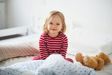 Happy Toddler Girl In Striped Red And White Pajamas Sitting On Bed Right After Awaking