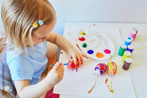 Obraz Adorable little girl painting eggs for Easter - fototapety do salonu