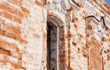 A Fragment Of The Outer Wall With Windows Of An Old Building Made Of Red Crumbling Bricks With Whitewash On A Bright Sunny Day. Selective Focus.