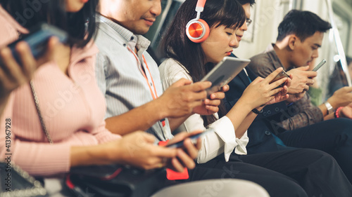 Fototapeta Young people using mobile phone in public underground train . Urban city lifestyle and commuting in Asia concept . obraz