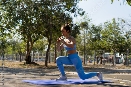 Asian woman Healthy She exercises outdoors, she does leg lunge poses Wallpaper Mural