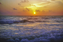 Sunset Over The Indian Ocean. The Sky Is Colored Orange. Light Clouds. Surf Waves Roll Onto The Beach With Foam And Spray. Shri Lanka