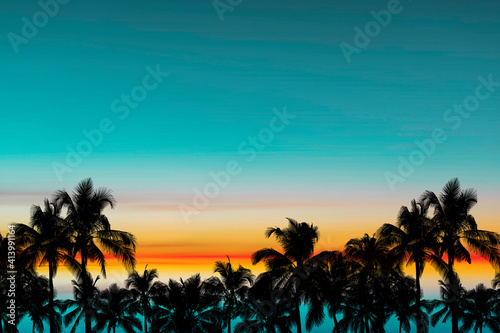Foto Silhouette coconut palm trees with blue sky after sunset on sea background