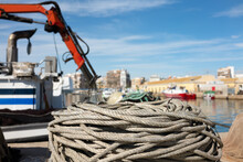 A Thick Rope Is Rolled Up On The Quay Wall In Front Of A Fish Trawler. On The Left Is A Board Crane. A Ship And Parts Of The City Can Be Seen In The Background With Beautiful Bokeh.