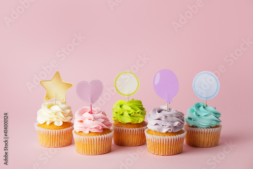 Tasty cupcakes with stylish toppers on color background © Pixel-Shot