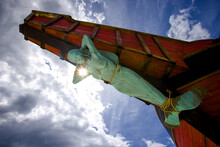 A Statue Of A Mermaid Tied Up To The Bow Of A Ship With Blue Sky And Clouds In The Background