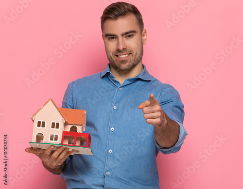 Slika na platnu portrait of casual man holding house model and pointing fingers