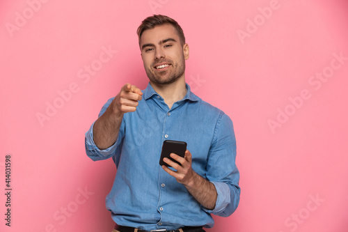 confident young guy in denim shirt pointing fingers and holding phone © Viorel Sima