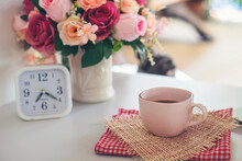 Coffee Break Time. A Cup Of Coffee, Rose Flower Vase, And Clock Place On White Home Office.