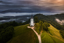 Jamnik, Slovenia - Aerial Drone View Of A Foggy Summer Sunrise At Jamnik St.Primoz Church. The Fog Gently Goes Around The Small Chapel With Colorful Sky And Julian Alps At Background