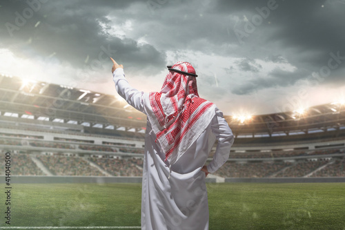 Arabian businessman back view standing on his stadium during sport match. Modern saudi lifestyle. Man in traditional wear looks confident, busy. Ethnicity, finance, income uncrease, sport, real estate © master1305