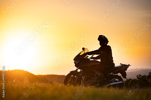 Slika na platnu Man on his motorbike riding into sunset