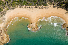 Aerial View Of A Wild Rocky Beach With Ocean Waves Crashing On The Sand, Queensland, Australia.