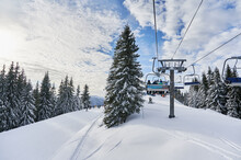 Panorama Of Snowy Hills With Coniferous Trees, Ski Lifts And People Under Blue Cloudy Sky. Scenery Of Snow-covered Slopes With Chairlift Mechanism For Transporting Skiers. Concept Of Ski Resort.