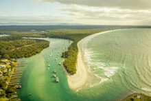 Aerial View Of A Small Boats Fleet Sailing The Currambene Creek At Sunset, Huskisson, New South Wales, Australia.