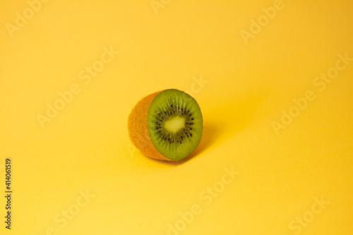 Half of kiwi on an orange background with trendy sunlight. Wallpaper Mural