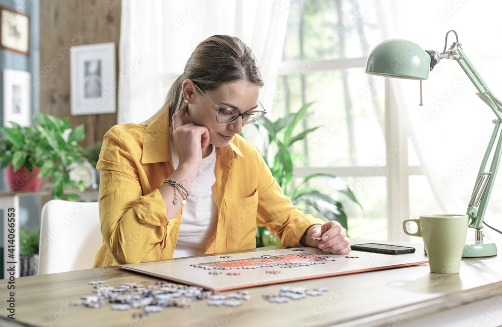 Fototapeta Woman sitting at desk and solving a puzzle