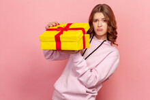 Portrait Of Displeased Teenage Girl In Hoodie Opening Birthday Gift On Party Celebration, Looking Disappointed Unhappy. Indoor Studio Shot Isolated On Pink Background