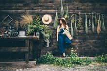 Attractive Girl Wearing Straw Hat And Blue Denim Dungarees Relaxing Near Wooden Old Summerhouse Wall On Sunny Day.