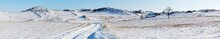 Panoramic View On Snowy Dirt Road On The Tazheran Steppe With Snow-covered Hills. Baikal Region, Olkhon District. Winter Landscape. Natural Wide Background, Banner. Outdoors And Winter Travel