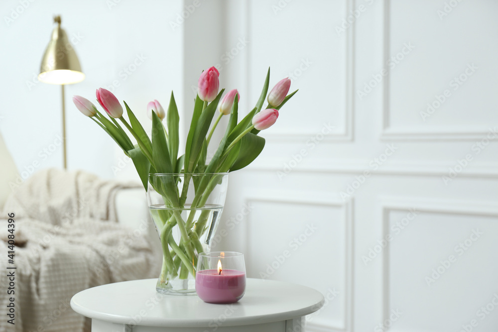 Fototapeta Beautiful tulips and burning candle on white table indoors, space for text. Interior design
